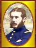 Gold-framed portrait of a white man with brown hair, mustache, and bushy sideburns with his arms crossed. He is wearing a blue military jacket with yellow buttons down the center and a yellow patch on the shoulder.