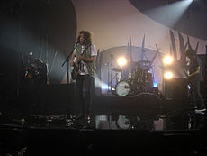 A performance shot of four men on stage. The man at left is turned away to his right, standing in a darkened area and holding a guitar almost vertically. The second man is singing into a microphone while playing a guitar. Behind and to his left is the drummer obscured by his kit. The last man is also shown in left profile and plays a guitar. Behind the performers is stage and lighting equipment.