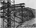 """""""The gravel 'ladders' from the plant conveyors to the tunnel underneath and the 48-inch belt running to the mixer... - NARA - 294031.tif"""