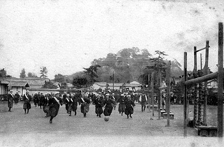 Japanese high-school girls playing football in their traditional hakama with one team wearing sashes. (c. 1920) Wan Gui Gao Xiao 4.jpg