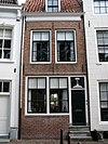 foto van Huis met gepleisterde lijstgevel. Nok evenwijdig aan straat. Dakkapel