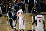 Two opposing basketball teams on a basketball court with a team in dark blue uniforms at the free throw line. One team is in white uniforms with names on the back and the other is dark blue with the word Michigan on the front and names on the back.
