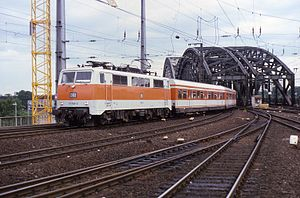 Rhine-Ruhr S-Bahn - A Class 111 locomotive leads an orange-and-white S-Bahn service across the Hohenzollernbrücke into Köln Hauptbahnhof in 1985