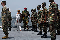 A colour photograph of soldiers on a naval vessel being inspected by President Ellen Johnson Sirlef and a senior military officer. The soldiers are wearing disruptive pattern camouflage uniforms and are standing in ranks across the deck