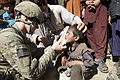 A U.S. Soldier, left, attached to Alpha Company, 1st Battalion, 179th Infantry Regiment, 45th Infantry Brigade Combat Team, provides medical aid to a local child, in the Dowlat-Shah district, Laghman province 111115-A-VR318-016.jpg