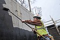 A contractor working on the Arlington National Cemetery's Millennium Expansion project, rolls sealant on the concrete wall of a bridge at the site.jpg
