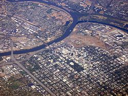 High angled aerial shot of a developed city; a suburban grid dominates the lower half of the image. A river bisects the city from the left before forking; the first fork continues up and to the right edge of the image; the second curves up and around to finish on the left, enclosing industrial units and other domestic properties.