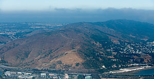 San Bruno Mountain - Aerial view of San Bruno Mountain from the east. The buildings on the mountainside on the right are part of Brisbane.