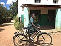 African girl in her school uniform riding her bicycle barefooted.jpg