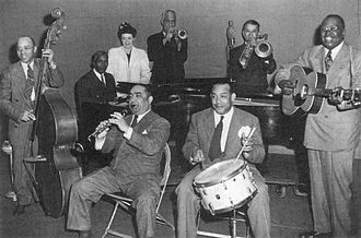 Crescent Records - The All Star Jazz Group, early 1944 (left to right): Ed Garland (bass), Buster Wilson (piano), Marili Morden (proprietor, Jazz Man Records), Jimmie Noone (clarinet), Mutt Carey (trumpet), Zutty Singleton (drums), Kid Ory (trombone), Bud Scott (guitar)