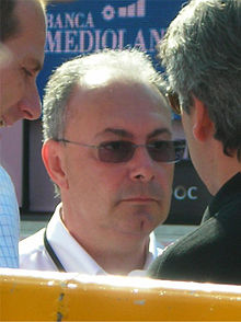 A man in his fifties, visible only from the neck up, wearing glasses with tinted lenses and a white polo shirt. Two other men are partly visible on either side of him.