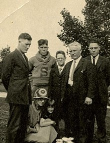 Five males of varying ages stand in a tight group, outdoors. Two sitting females huddle with them: a woman in a dress and a 1920s-style bonnet and a young girl in a dress. All have somber expressions. All the males wear jackets and suit ties with the exception of a teenage youth in a collared shirt and loop-collared, pullover sweater with a large block letter sewn onto the sweater's front.