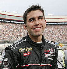 Almirola, with spiked hair, smiles at the camera while wearing his black racing suit. The filled grandstands are in the background.