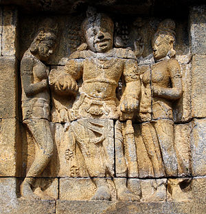 Asura (Buddhism) - The guarding figure Asura giant dvarapala holding mace flanked by two apsaras. The bas-relief of lower outer wall of Borobudur separating Kamadhatu and Rupadhatu realm. 8th century Central Java, Indonesia.