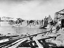 Ein mit Truppen beladenes Landungsboot macht in einem beschadigten Hafen fest