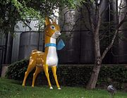 Statue with a stylistic representation of a deer in yellow and white with a blue ribbon around its neck.