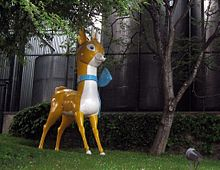 Statue with a stylistic representation of a deer in yellow and white with a blue ribbon round its neck.