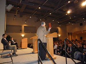 Dan Barker - Barker with a red Bible, debating Dinesh D'Souza at UCSD in 2011.