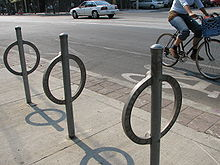 Unpainted steel rings, each welded to a steel post (running through it), set in concrete slabs. A cyclist is passing by from left to right on the cycle path behind.
