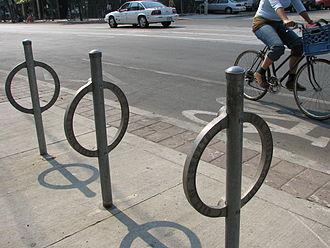 Неокрашенные стальные кольца, каждое приваренное к стальному столбу (проходящему через него), установленное в бетонных плитах. Велосипедист проезжает слева направо по велосипедной дорожке позади.