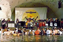 A crowd of people standing in water and listening to a band perform on stage