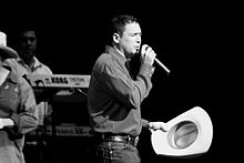 A black and white photo of Pulido wearing a dress shirt tucked in jeans with his cowboy hat on one hand and a microphone on the other. A Keyboardist and his instrument can be seen in the foreground of the photo.