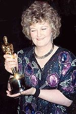 A picture of a curly-haired woman wearing a dress with various purple and green prints. She is holding a golden statuette.