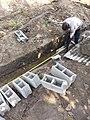 Bricklayer taking measurements.jpg