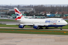 A British Airways Boeing 747‑400 in Oneworld livery taxiing on the taxiway, with Heathrow Airport facilities in the background and green grass patch in the foreground