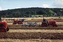 Brown field being ploughed by multiple red tractors. In the background it a hill with trees.