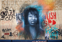 Mural of a young woman and graffiti on the other side of a chain-link fence