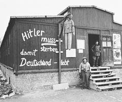 Photo noir et blanc de l'entrée d'une baraque en bois dans le camp de concentration de Buchenwald. Au centre de la photo, près du mur de la baraque, se dresse une potence à laquelle pend un pantin à l'effigie d'Adolf Hitler. Sur le mur de la baraque est peinte l'inscription en allemand: «Hitler muss sterben damit Deutschland lebt». À droite, un homme, en tenue sombre, se tient debout dans l'encadrement de la porte, au sommet de l'escalier en bois qui mène à l'entrée. Un soldat américain pose debout à côté de l'escalier.