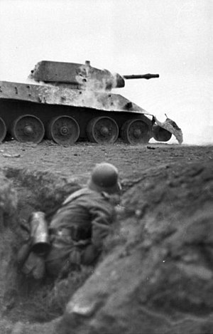 Kamenets-Podolsky pocket - A German soldier takes cover near a knocked out T-34, March 1944