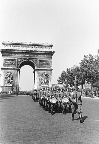 German military administration in occupied France during World War II - German soldiers march by the Arc de Triomphe on the Avenue des Champs-Élysées in Paris (June 1940).