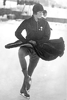 A female figure skater wearing a dark-colored dress and cloche hat performs a turn in an outdoor ice rink.