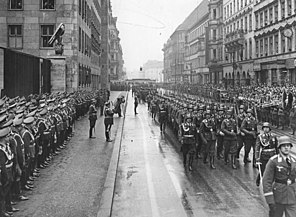 Soldiers with rifles and helmets march along a road past a reviewing party and guard of honor