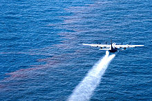 A large four propeller airplane sprays Corexit onto oil-sheen water