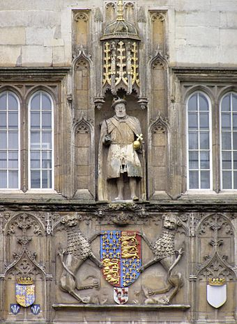 The statue of the college's founder Henry VIII presiding over the Great Gate, with a chair leg in his right hand CambridgeTrinityGreatGate.JPG