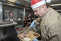 Capt. Larry McCullen serves Christmas dinner. (39282283442).jpg