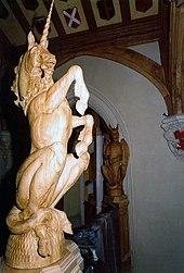 Foto temigante grandan lignoskulptaĵon de unikorno, erektante sur siaj malantaŭaj kruroj. Malantaŭ ĝi parto de muro kaj plafono povas esti vidita, ĉi-lasta ornamis per heraldikaj ŝildoj.