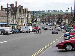 The wide main street of Chipping Sodbury. Cars are parked where market stalls would once have been.
