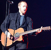 A man wearing a blue t-shirt and dark blue jacket holding a guitar and standing behind a microphone stand.