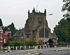 A cruciform church with a broad central tower; this is crenellated and has prominent buttresses; in front is a lych gate and a white railing; in the foreground is a lamppost and a road with traffic islands