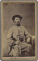 Sepia photo shows a seated man with a moustache wearing a black hat and a light gray military uniform.