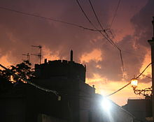 Coria sunset after rain.  Sun is setting behind black silhouette of castle; and it lights heavy dark clouds from below