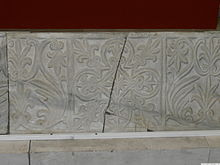 A stone block entirely covered by carvings of two alternating floral motifs, separated into square sections
