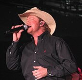 A man in a black shirt and cowboy hat, singing into a microphone