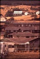 DWELLINGS OF KING CITY CLING TO SHELTER OF HILL, FARMLANDS RISE STEEPLY BEHIND THEM - NARA - 545205.tif