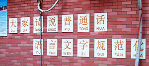 Pinyin - A school slogan asking elementary students to speak Putonghua is annotated with pinyin, but without tonal marks.