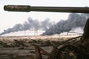 Disabled Iraqi T-54A, T-55, Type 59 or Type 69 tank and burning Kuwaiti oil field.jpg